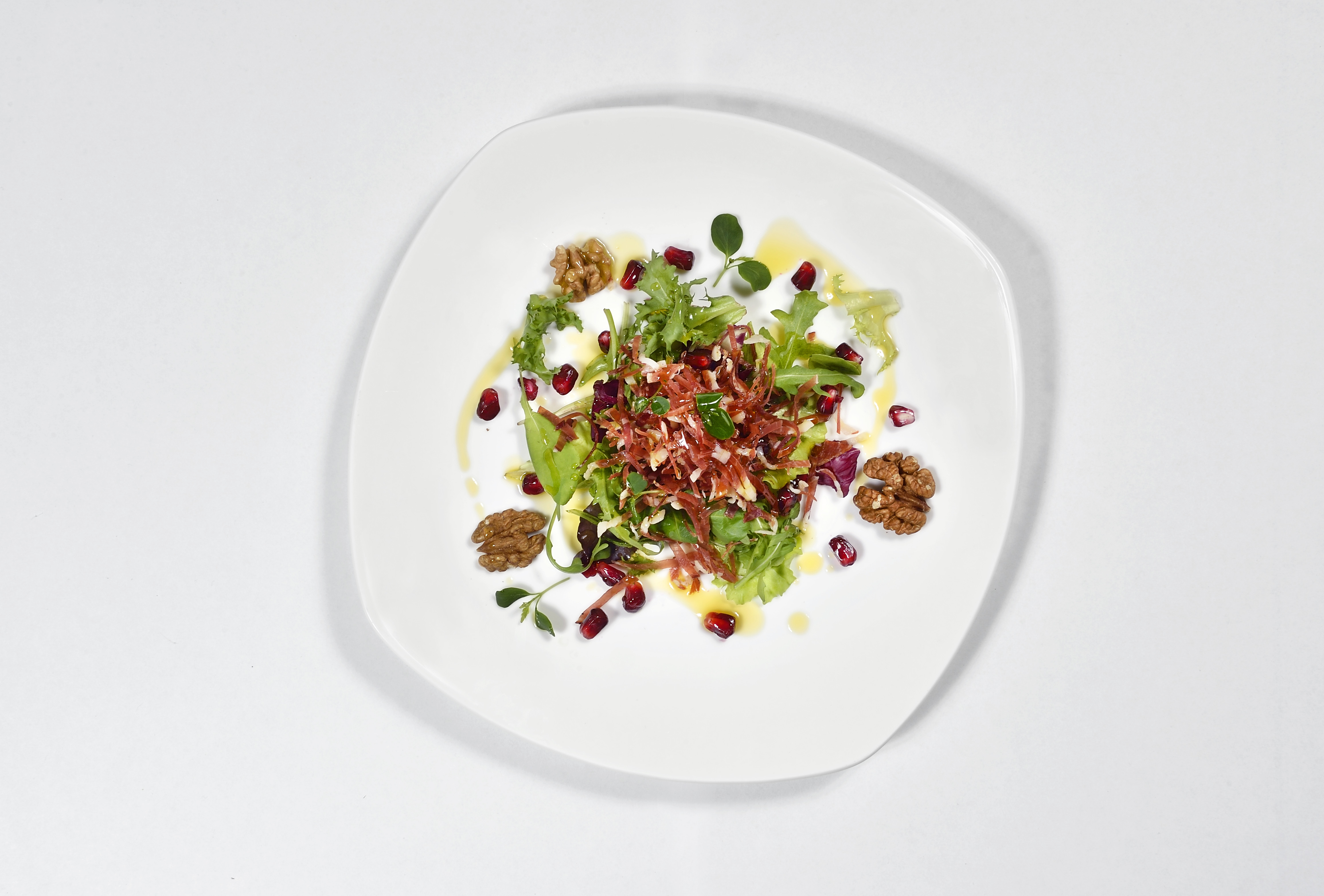 Bouquet of mixed leaf lettuce with pomegranate pearls, crunchy filets of speck and walnuts 1